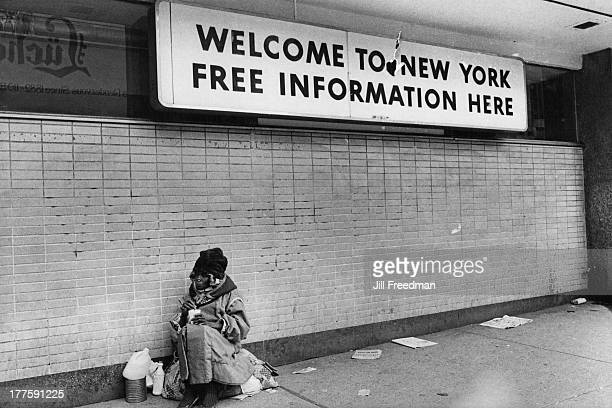 A homeless woman sits with her belongings below a sign reading 'Welcome To New York Free Information Here' Times Square New York City 1976