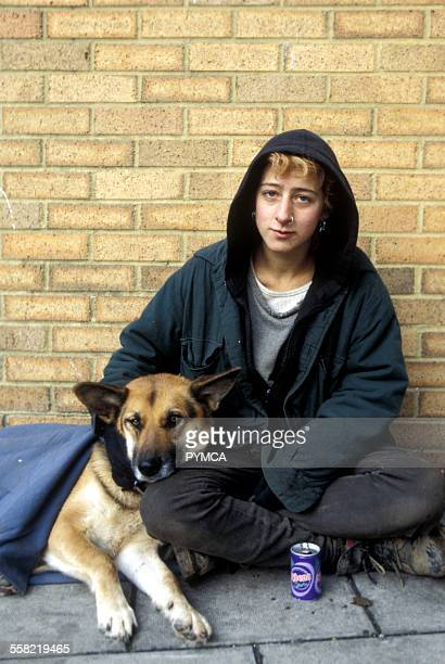 Homeless woman sitting on the street with her dog