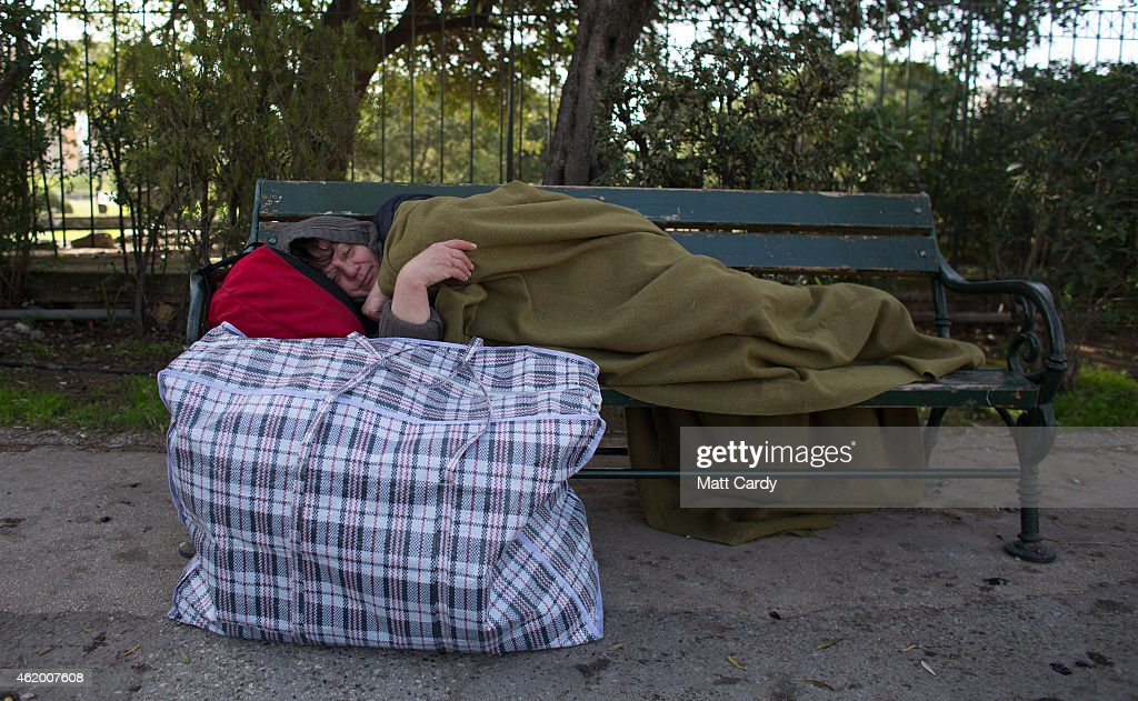 A homeless woman sleeps on a park bench ahead of the general election on Sunday on January 23, 2015 in Athens, Greece. According to the latest opinion polls, the left-wing Syriza party are poised to defeat Prime Minister Antonis Samaras' conservative New Democracy party in the election, which will take place on Sunday. European leaders fear that Greece could abandon the Euro, write off some of its national debt and put an end to the country's austerity by renegotiating the terms of its bailout if the radical Syriza party comes to power. Greece's potential withdrawal from the eurozone has become known as the 'Grexit'.