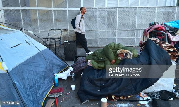 A homeless woman sleeps on a pile of belongings on the street near the Los Angeles Mission hosting its annual Christmas meal for the homeless on...