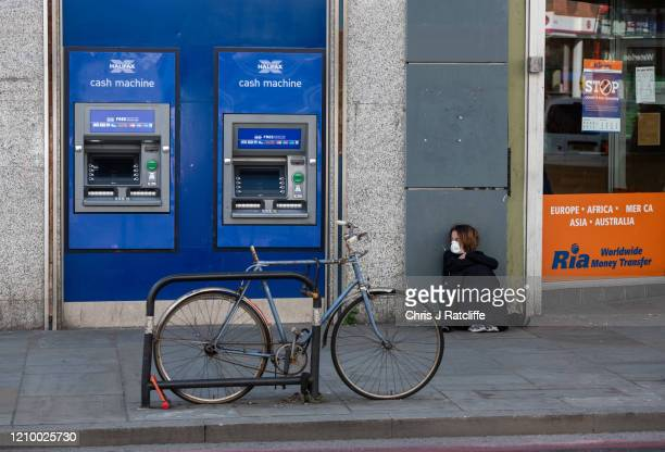 Homeless woman wearing a face mask sits next to cash machines and an international money transfer shop in Dalston Kingsland on April 15, 2020 in...