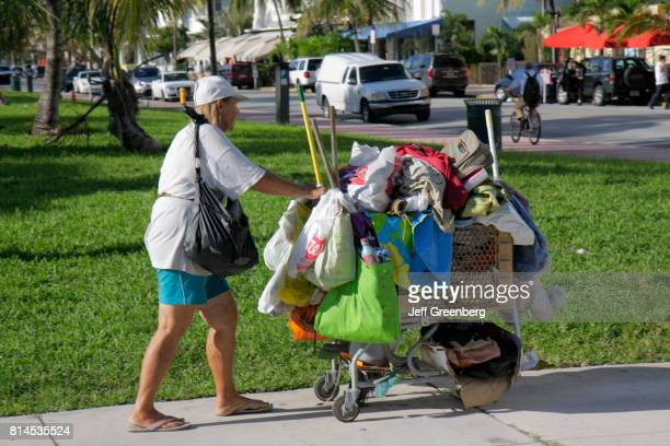 A homeless woman with a shopping cart of her possessions in Lummus Park