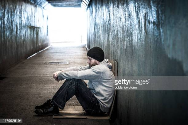 homeless young man sitting in cold subway tunnel - male bum stock pictures, royalty-free photos & images