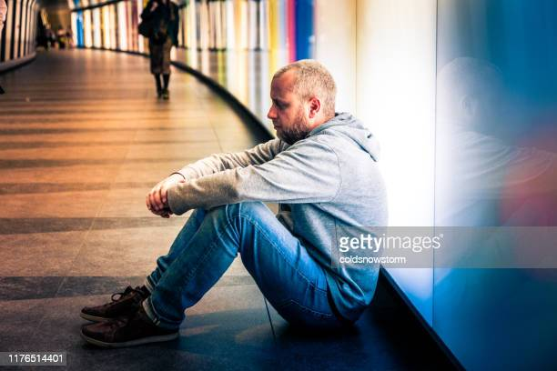 homeless young man sitting in futuristic illuminated subway tunnel in city - begging social issue stock pictures, royalty-free photos & images