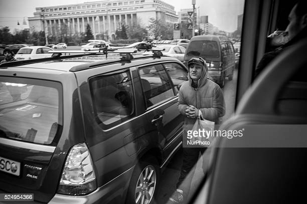 A homeless youth begging for money in traffic stopped at Piata Victoriei in central Bucharest Photo Jodi Hilton/NurPhoto