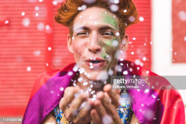 Homem blow confetti from hands