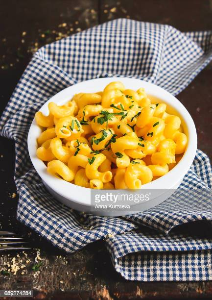 Homemade american dish mac and cheese with pumpkin and parsley in a bowl on a wooden table, selective focus