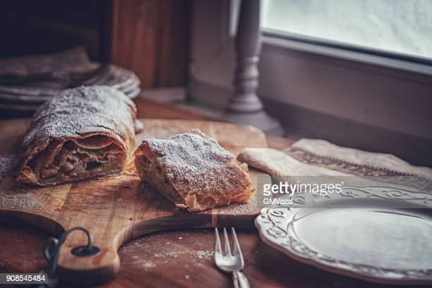 homemade apfelstrudel with powdered sugar - traditionally austrian stock pictures, royalty-free photos & images