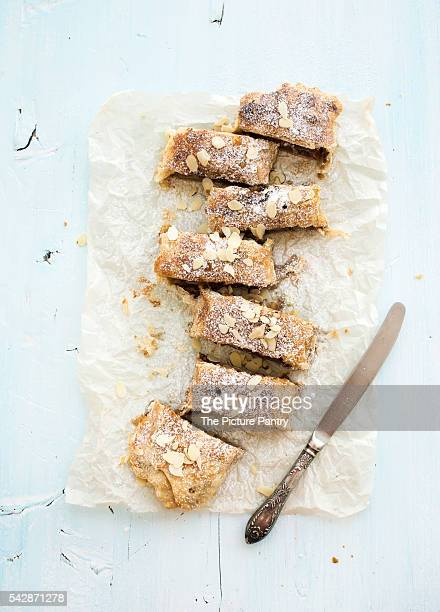 Homemade apple and almond strudel on baking paper over light blue wooden backdrop