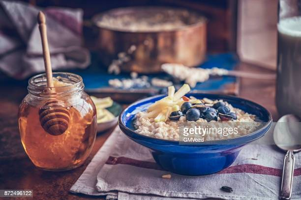 homemade apple blueberry porridge with honey - oatmeal stock photos and pictures