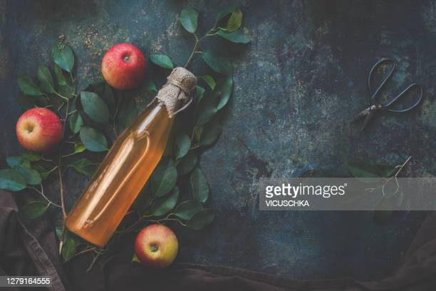 homemade apple cider vinegar on dark rustic background with apples - cider stock pictures, royalty-free photos & images