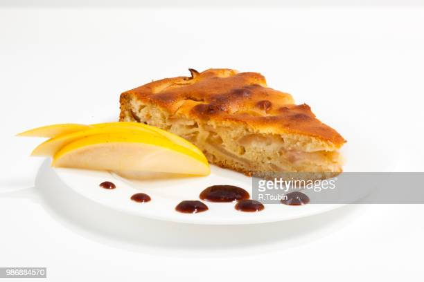 Homemade apple pie on a plate with jam and apple over white background