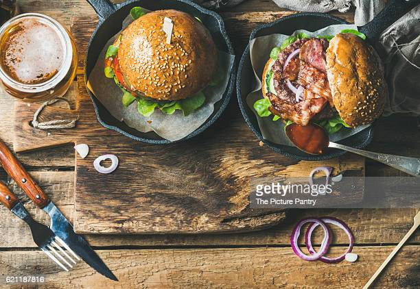 Homemade beef burgers with crispy bacon and fresh vegetables in small pans and glass of wheat beer on rustic serving board over shabby wooden background