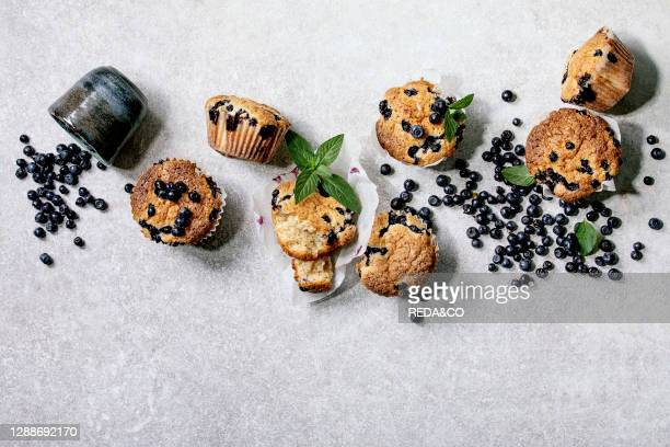 Homemade blueberry muffins in paper cupcake holder decorated by fresh berries and mint leaves on light grey background. Flat lay, copy space.