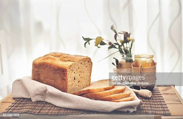 Homemade bread sliced on a dish towel in front of a window