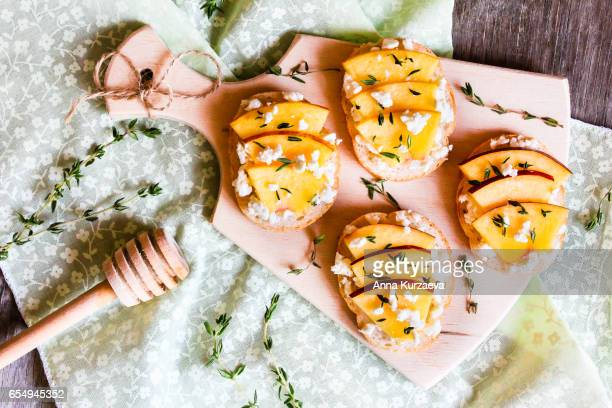 Homemade Bruschetta with nectarines, salted feta cheese, dried thyme and honey on a wooden board, selective focus
