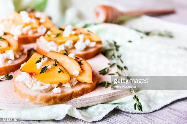 homemade bruschetta with nectarines, salted feta cheese, dried thyme and honey on a wooden board, selective focus - french food stock pictures, royalty-free photos & images