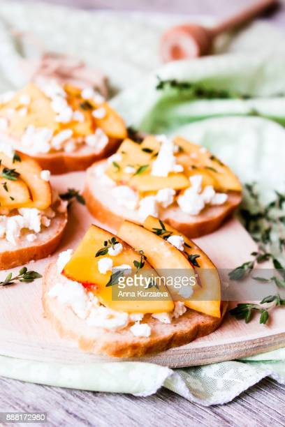 homemade bruschetta with nectarines, salted feta cheese, dried thyme and honey on a wooden board, selective focus - savory food stock pictures, royalty-free photos & images