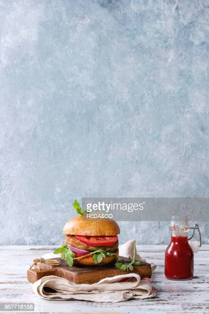 Homemade burger in classic bun with tomato sauce arugula meat cheese onion bottle of ketchup on wood serving board over white wooden plank table...