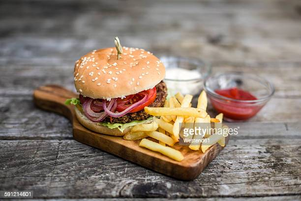 homemade burger with lettuce, meat, tomato, onion and french fries on chopping board - ハンバーガー ストックフォトと画像
