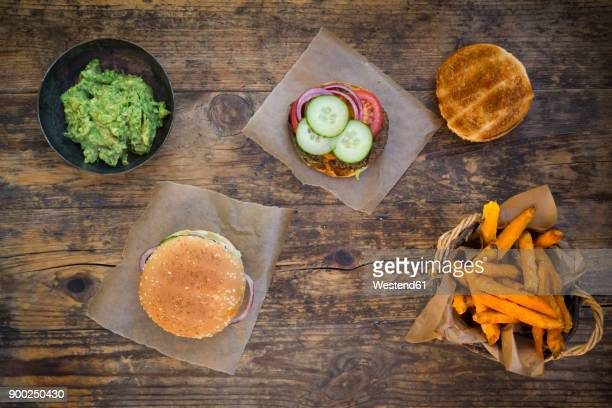 homemade burger with sweet potato fries and avocado dip - wax paper stock photos and pictures