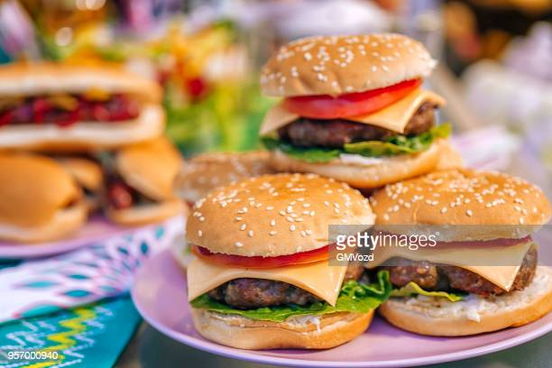 homemade burgers with tomatoes, onions and salad - cheeseburger stock pictures, royalty-free photos & images