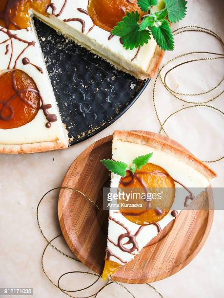 Homemade cake or pie with vanilla cottage cheese (cheesecake), ripe peaches and dark chocolate decorated with fresh mint leaves, top view