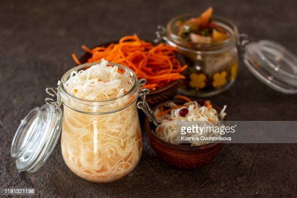homemade canned vegetables. pickled cucumbers, cauliflowers, carrots and peppers in glass jar. - fermenting stock pictures, royalty-free photos & images