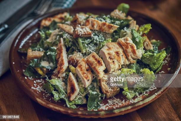 homemade cesar salad with chicken, lettuce and parmesan - romaine lettuce stock photos and pictures