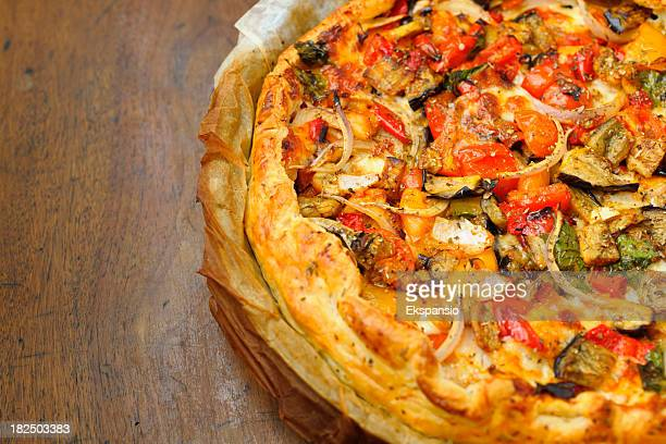 homemade cheese and vegetable pizza pie in greaseproof paper - savory pie stock photos and pictures