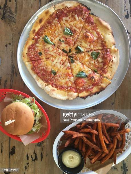 Homemade cheese pizza with a burger and fries