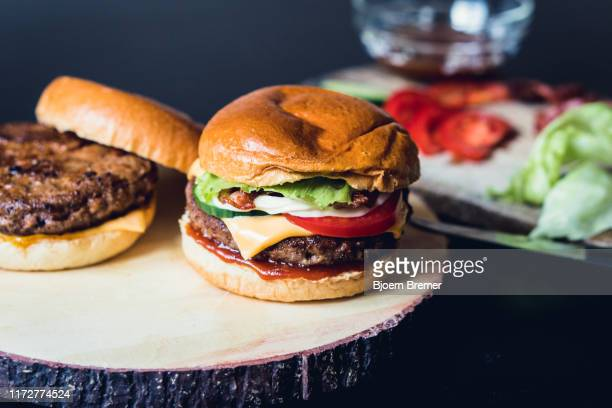 homemade cheeseburgers with ingredients in the background - hamburger stock pictures, royalty-free photos & images