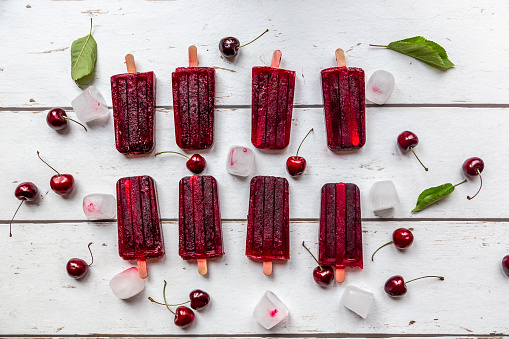 Homemade cherry ice lollies, ice cubes and cherries on white wood - gettyimageskorea