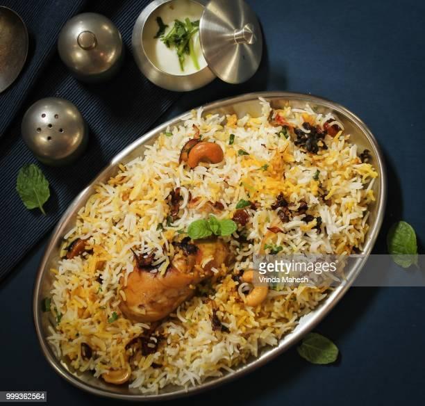 homemade chicken dum biryani served with raita, overhead view on dark blue background - biryani stock photos and pictures