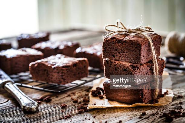 homemade chocolate brownies shot on rustic wooden table - brownie stock pictures, royalty-free photos & images
