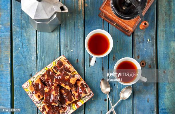 homemade chocolate cake and two cups of tea - coffee grinder stock photos and pictures