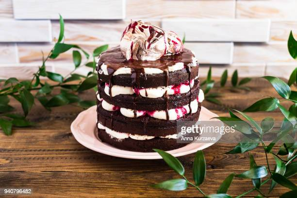 homemade chocolate cake called black forest cake with mascarpone cream and cherry topped with sweet meringues on a plate on a wooden table, selective focus - mascarpone cheese stock pictures, royalty-free photos & images