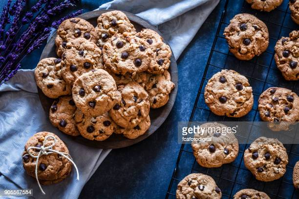 homemade chocolate chip cookies on dark kitchen table - chocolate chip cookie stock pictures, royalty-free photos & images