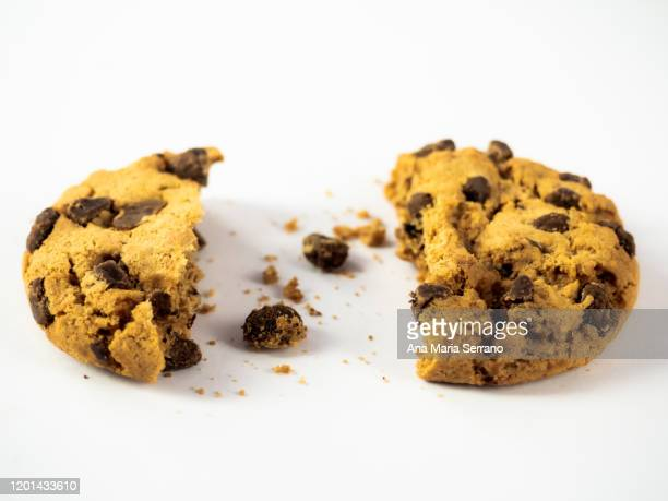 a homemade chocolate cookie with a bite and crumbs on a white background - sweet food stock pictures, royalty-free photos & images