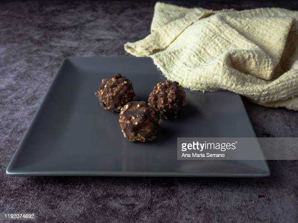 homemade chocolate crunchy chocolates with hazelnut pieces and nuts in a gray square plate on a dark background with a beige rustic cloth - course meal stock pictures, royalty-free photos & images