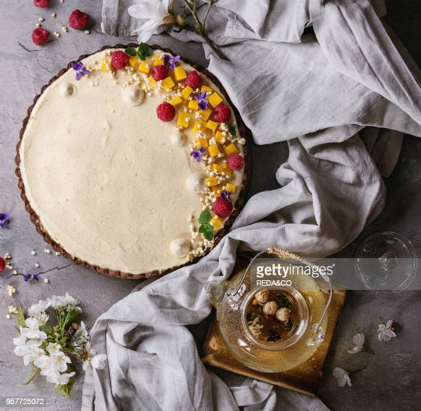 Homemade chocolate tart decorated by mango raspberries mint puffed rice and edible flowers served with glass teapot and textile linen over gray...