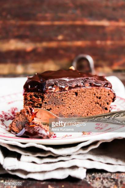 Homemade chocolate truffle brownie cake with chocolate cream spread on a plate on a wooden table. Sweet food. Easter cake.