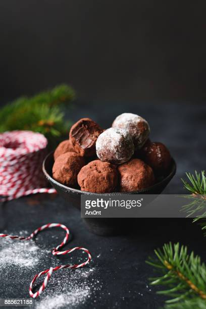 homemade chocolate truffles in black bowl. - chocolate pieces stock photos and pictures