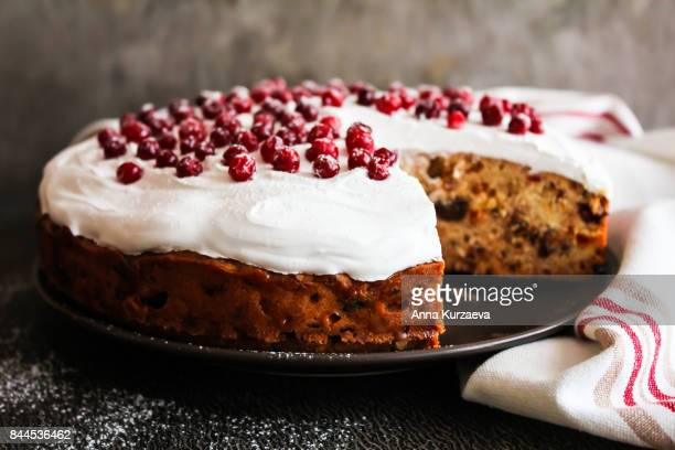 homemade christmas cake with dried fruits decorated with sweet vanilla meringue, fresh cranberry and icing sugar on a plate, selective focus - christmas cake stock photos and pictures