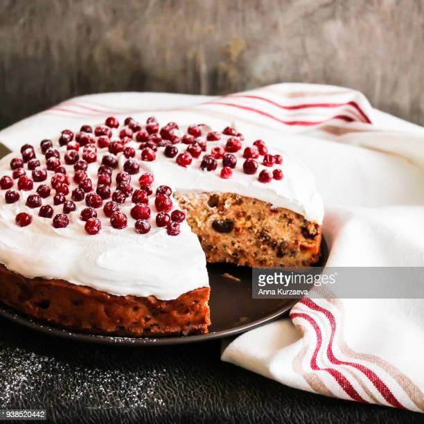 homemade christmas cake with dried fruits decorated with sweet vanilla meringue, fresh cranberry and icing sugar on a plate, selective focus. easter cake. - christmas cake stock photos and pictures