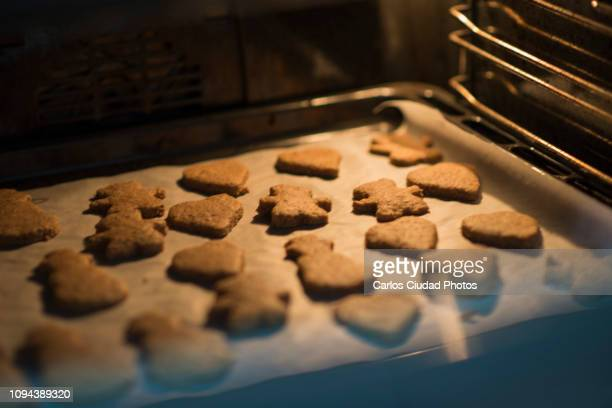 home-made christmas cookies baking in the oven - gingerbread cookie stock pictures, royalty-free photos & images