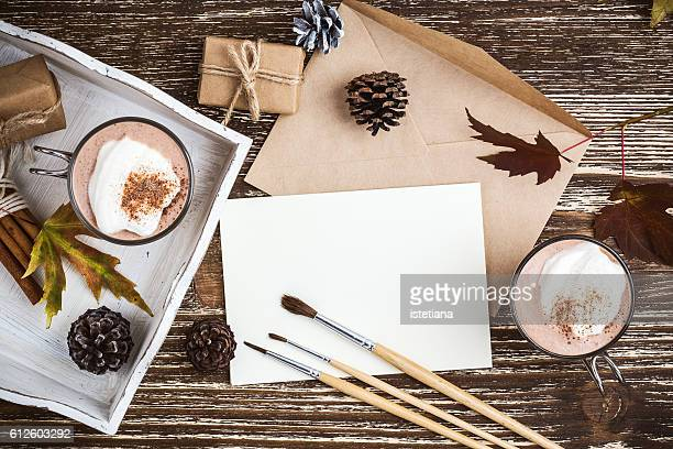 homemade cinnamon and spice hot cocoa served with whipped cream. thanksgiving table with envelope and blank card for holiday message viewed from above - happy thanksgiving card stock pictures, royalty-free photos & images