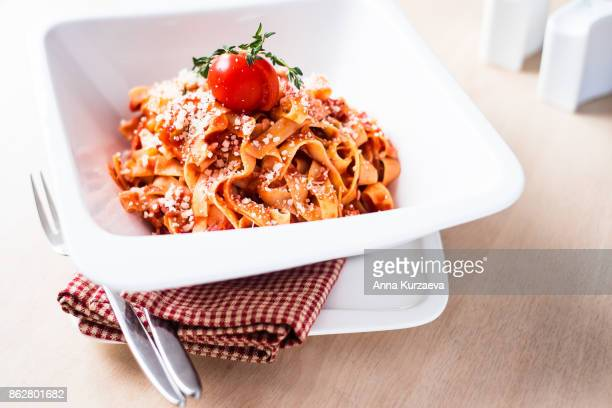 Homemade classic pasta tagliatelle with traditional italian bolognese sauce or ragu from minced pork and beef meat, carrot, celery, tomatoes served with freshly grated parmesan cheese, cherry tomato and fresh thyme in a plate, selective focus