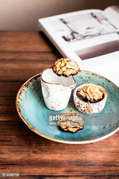 Homemade coconut macaroon cookies with dark chocolate sauce on a plate on a wooden table, selective focus