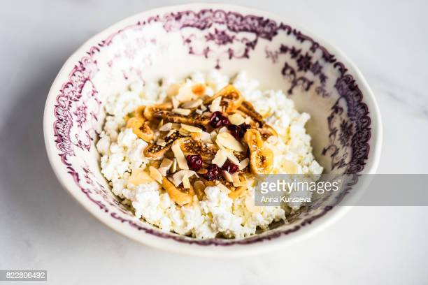 Homemade cottage cheese with dried fig, banana, berry, honey in a bowl, selective focus